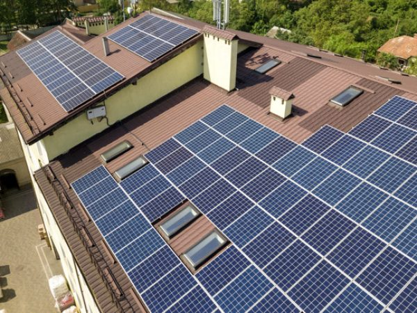 Aerial view of many solar panels mounted of industrial building roof.